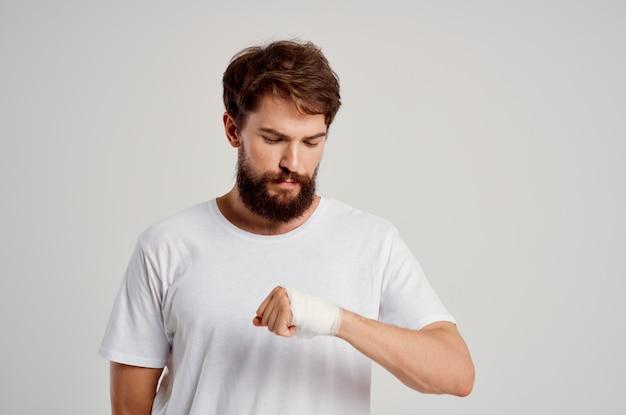 Mężczyzna pacjent zabandażowany uraz ręki do palców hospitalizacji na białym tle