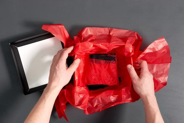 Mężczyzna pakowania pudełko z modną seksowną czerwoną bielizną na szarym drewnianym stole. zamknąć widok.
