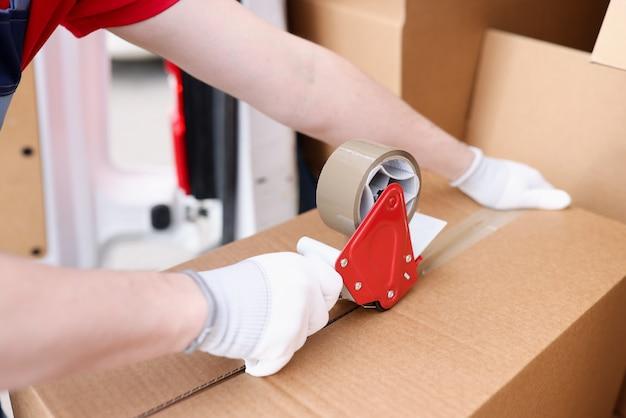 Mężczyzna pakujący kartonowe pudełko za pomocą dozownika taśmy samoprzylepnej zbliżenia