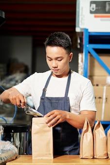 Mężczyzna pakujący ziarna kawy na sprzedaż