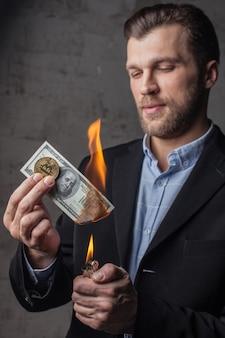 Mężczyzna palący studolarowy banknot i trzymający bitową monetę