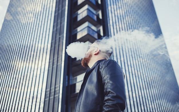 Mężczyzna pali papierosa elektronicznego