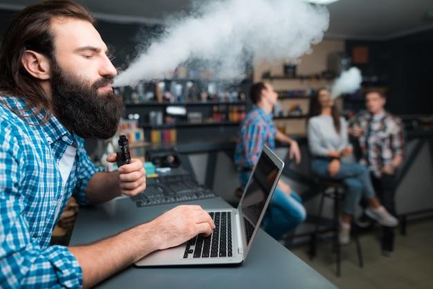 Mężczyzna pali papierosa elektronicznego.