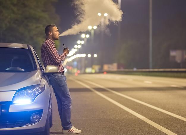 Mężczyzna pali papierosa elektrycznego w pobliżu samochodu na drodze. wieczorna pora nocna