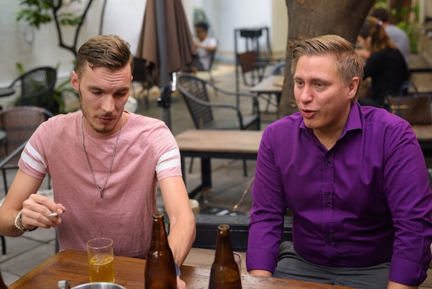 Mężczyzna pali papierosa podczas picia piwa z przyjaciółmi