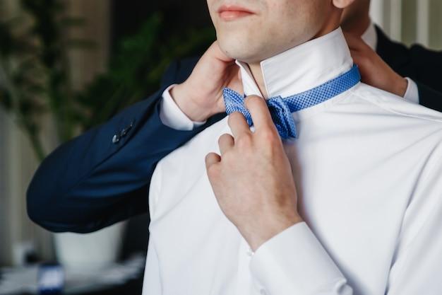 Mężczyzna, pan młody w białej koszuli na tle mieszkania. ślub, zgromadzenie pana młodego, stworzenie rodziny.