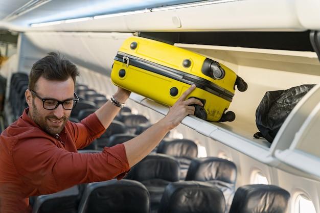 Mężczyzna pasażer trzyma walizkę i kładzie ją na półce w samolocie