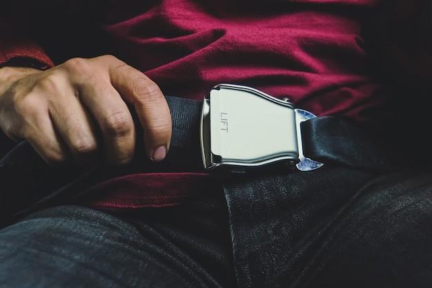 Mężczyzna pasażera zwalniania pasów bezpieczeństwa siedząc w samolocie przygotowując się do wysiadania. koncepcja bezpiecznego lotu. bezpieczeństwo podczas jazdy. turbulencje podczas lotu