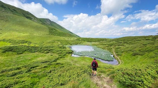 Mężczyzna patrząc na górskie jezioro w drahobrat, karpaty, ukraina
