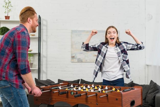 Mężczyzna patrząc na jej dziewczynę, wiwatując po zwycięstwie w piłkarzyki