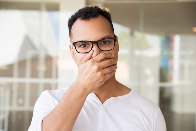Mężczyzna patrząc na kamery, zamykając usta ręką, patrząc zszokowany