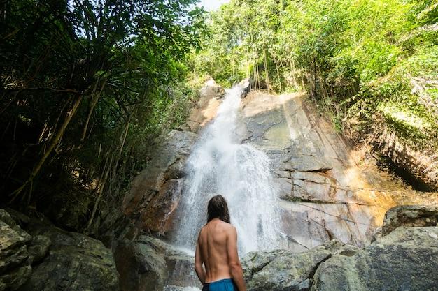 Mężczyzna patrząc na tropikalny wodospad