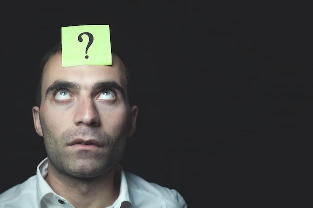 Mężczyzna patrząc w górę. karteczkę ze znakiem zapytania