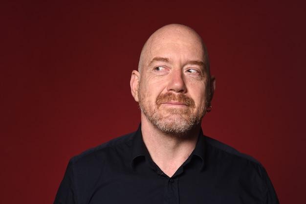 Mężczyzna patrząc z boku na czerwonym tle, uśmiechając się