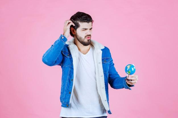 Mężczyzna patrzący na mini kulę ziemską i myślący
