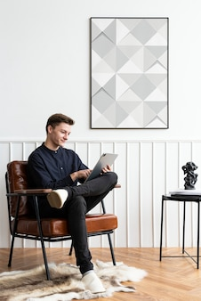 Mężczyzna patrzący na tablet w swoim salonie