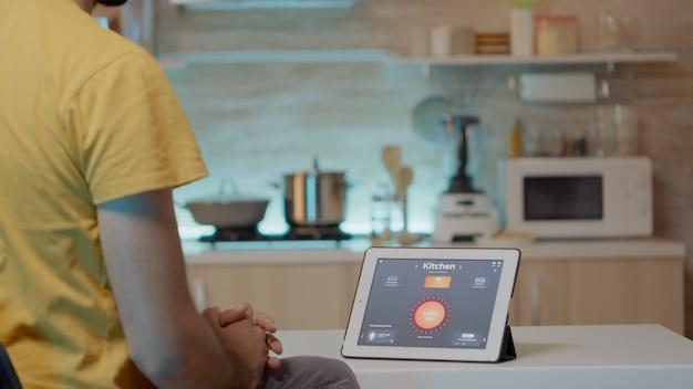 Mężczyzna patrzący na tablet z inteligentnym oprogramowaniem umieszczonym na stole kuchennym kontrolującym światło o wysokiej ...