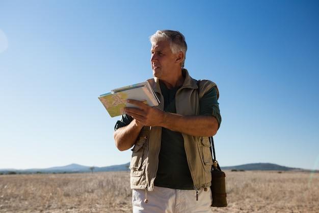 Mężczyzna patrzeje daleko od na krajobrazie z mapą