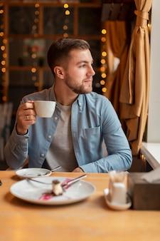 Mężczyzna patrzeje daleko od z filiżanką kawy