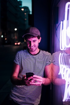 Mężczyzna patrzeje jego uśmiech i telefon