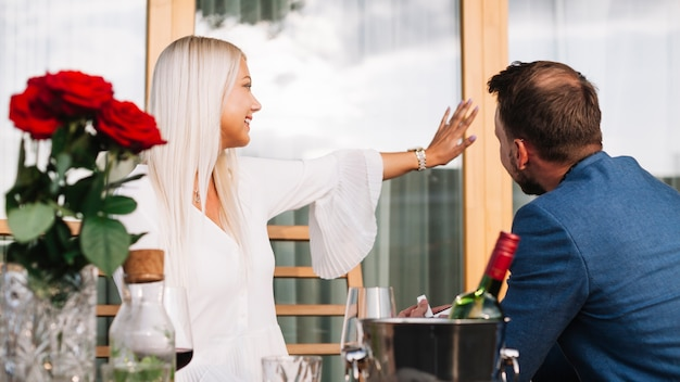 Mężczyzna patrzeje jej dziewczyny pokazuje diamentowego pierścionek w restauraci