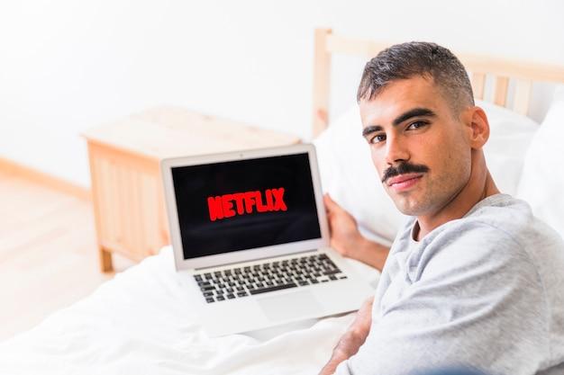 Mężczyzna patrzeje kamerę podczas gdy oglądający netflix serie