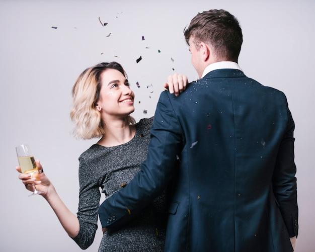 Mężczyzna patrzeje kobietę z szampańskim szkłem w kostiumu