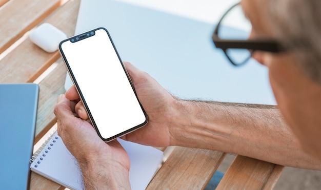 Mężczyzna patrzeje mądrze telefon z pustym bielu ekranem