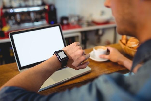 Mężczyzna patrzeje mądrze zegarek przy kawiarnią