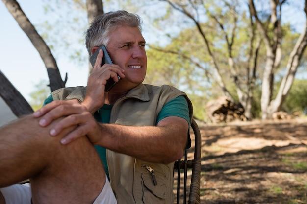 Mężczyzna patrzeje oddalony podczas gdy opowiadający na telefonie