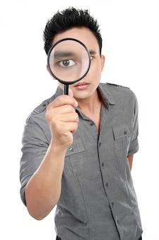Mężczyzna patrzeje przez powiększać - szkło