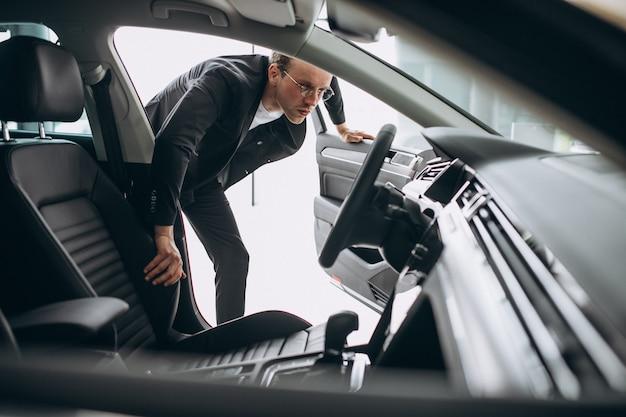 Mężczyzna patrzeje samochód w samochodowym salonie wystawowym