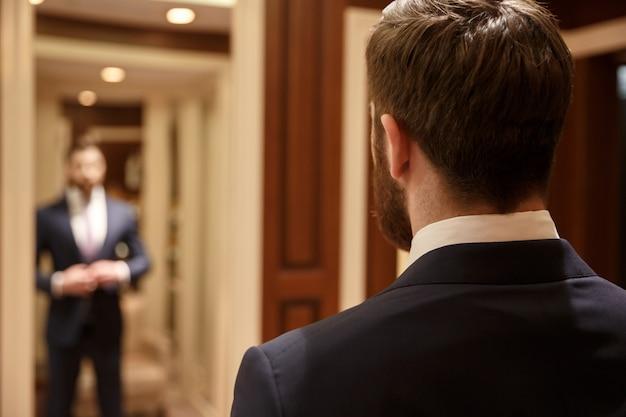 Mężczyzna patrzeje w lustrze jest ubranym kostium