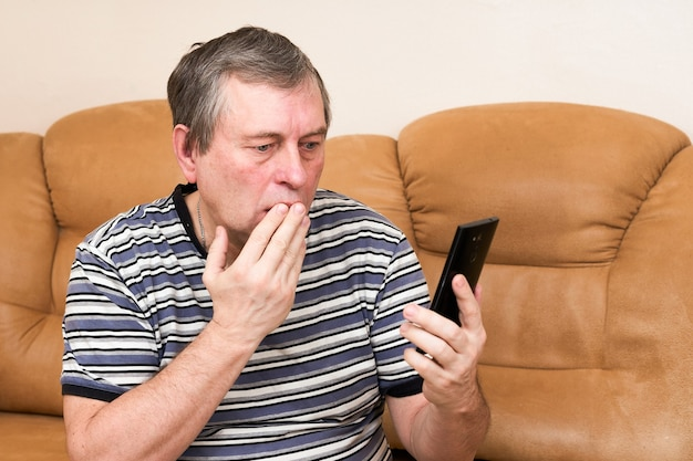 Mężczyzna patrzy emocjonalnie w smartfona siedząc na kanapie