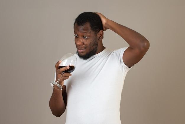 Mężczyzna patrzy na kieliszek wina w swojej dłoni, stojąc przed szarą ścianą