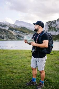 Mężczyzna patrzy na mapę w górskim krajobrazie