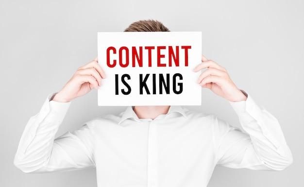 Mężczyzna patrzy na twarz białą kartką z tekstem content is king