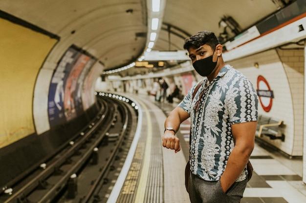 Mężczyzna patrzy na zegarek i czeka na pociąg na peronie
