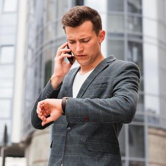 Mężczyzna patrzy na zegarek i rozmawia przez telefon w drodze do pracy