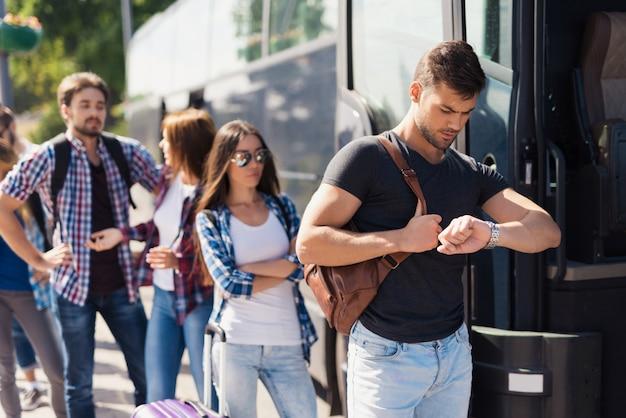 Mężczyzna patrzy na zegarek i wsiada do autobusu.