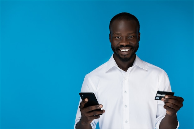 Mężczyzna patrzy w kamerę i trzyma telefon i kartę kredytową