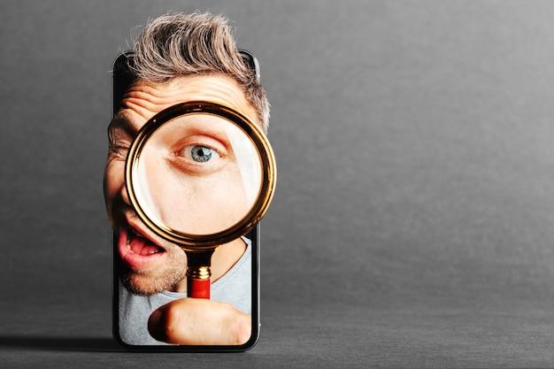 Mężczyzna patrzy w lupę przez telefon komórkowy