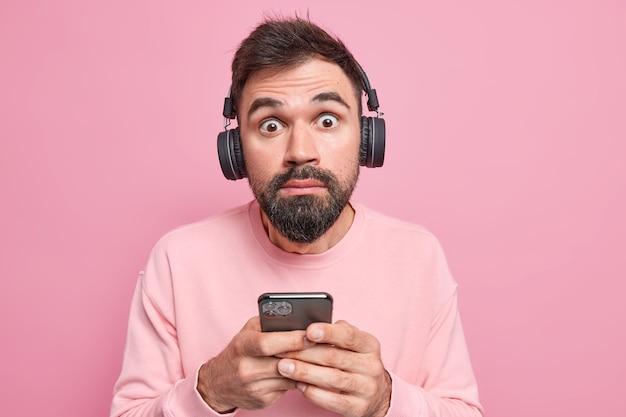 Mężczyzna patrzy wyłupiastymi oczami na aparat używa telefonu komórkowego słucha ścieżki dźwiękowej przez bezprzewodowe słuchawki, ubrany w zwykłe ubranie