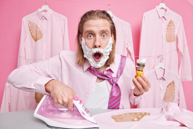 Mężczyzna patrzy z wyrazem omg, prasuje ubrania na desce do prasowania i jednocześnie goli sukienki na randkę