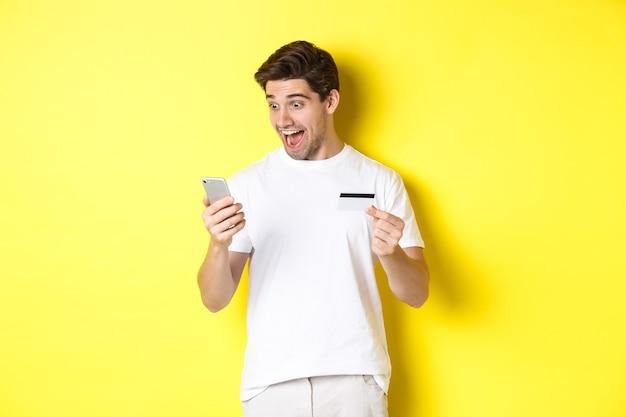 Mężczyzna patrzy zaskoczony na smartfona, robi zakupy online, trzyma kartę kredytową, stoi nad żółtą ścianą
