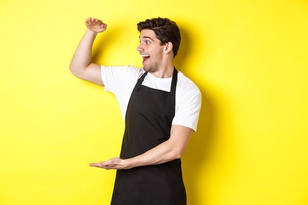 Mężczyzna patrzy zdziwiony na coś dużego, stojącego w czarnym fartuchu na żółtej ścianie