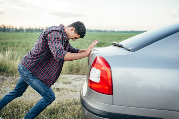 Mężczyzna pcha uszkodzony samochód, widok z boku. pojazd z kłopotami na poboczu w letni dzień