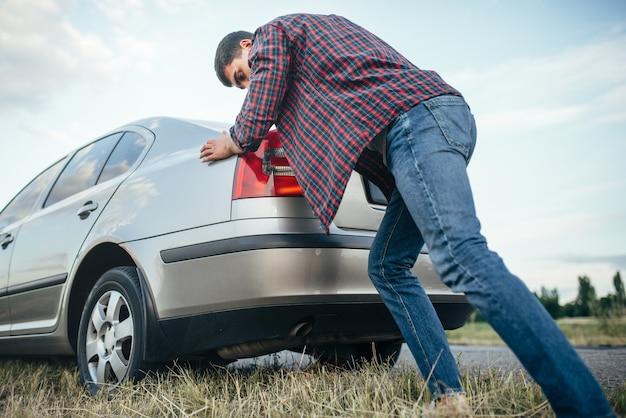 Mężczyzna pcha uszkodzony samochód, widok z boku