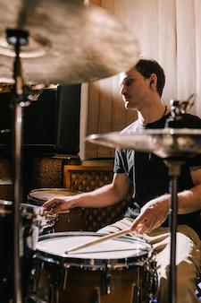 Mężczyzna perkusista grający na perkusji w studiu nagraniowym