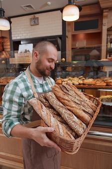 Mężczyzna piekarz niosący świeżo upieczony chleb w koszu